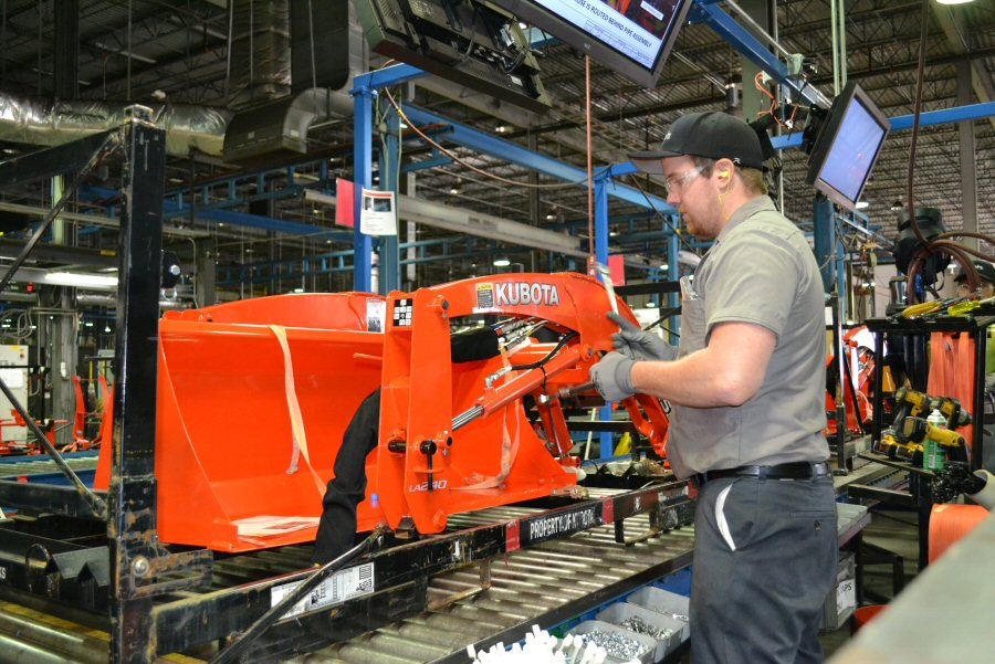 An employee is hard at work assembling a loader.