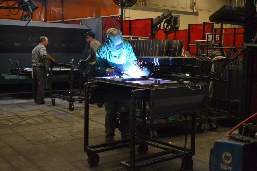 An employee is welding together parts to begin the process.