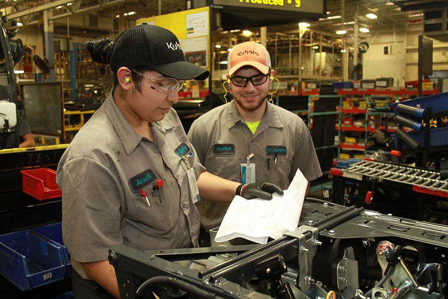 A team lead helps an employee go over their check sheet on the production line.