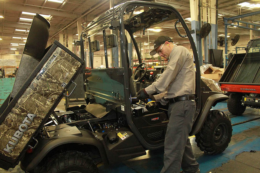 An employee is doing some final assembly on an RTV unit.