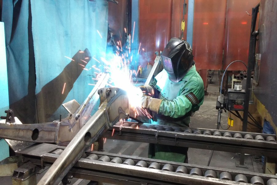 Welders working on implements in the weld shop at KIE.
